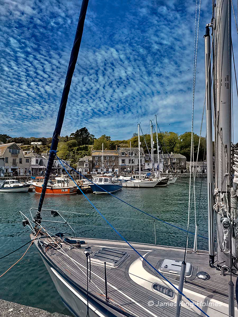 Looking across the harbour at Padstow, Cornwall from the South Quay towards The Strand, with a moored sailing boat in the foreground. Cirrocumulus clouds give the sky an appearance of fish-scales, hence the term 'mackerel sky' = appropriate for a fishing harbour.