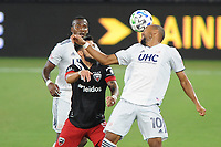 WASHINGTON, DC - AUGUST 25: Teal Bunbury #10 of New England Revolution heads the ball against Junior Moreno #5 of D.C. United during a game between New England Revolution and D.C. United at Audi Field on August 25, 2020 in Washington, DC.