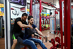 bodybuilder Palestinian, Nidal al-Daour 30, who lost his arm, trains during an exercise session, at his gym, in Beit Lahia, in the northern Gaza Strip, on April 12, 2021. Al-daour lost his arm during the 2008 war during his career as a medic. He workes a trainer in bodybuilding, and opened a gym, where he made a special device to be able to lift weights. Photo by Mohammed Salem