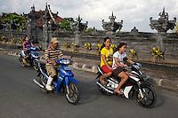 Bali, Indonesia.  Men and Women on Motorbikes, no Helmets.