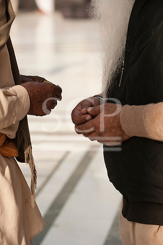 Amritsar, Punjab, India. Two old men praying, their hands clasped close together, one with a long beard.