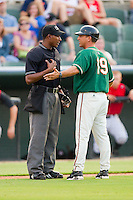 Home plate umpire Ramon DeJesus discusses a call with Greensboro Grasshoppers manager Andy Haines #19 during a South Atlantic League game between the Greensboro Grasshoppers and the Kannapolis Intimidators at Fieldcrest Cannon Stadium August 2, 2010, in Kannapolis, North Carolina.  Photo by Brian Westerholt / Four Seam Images