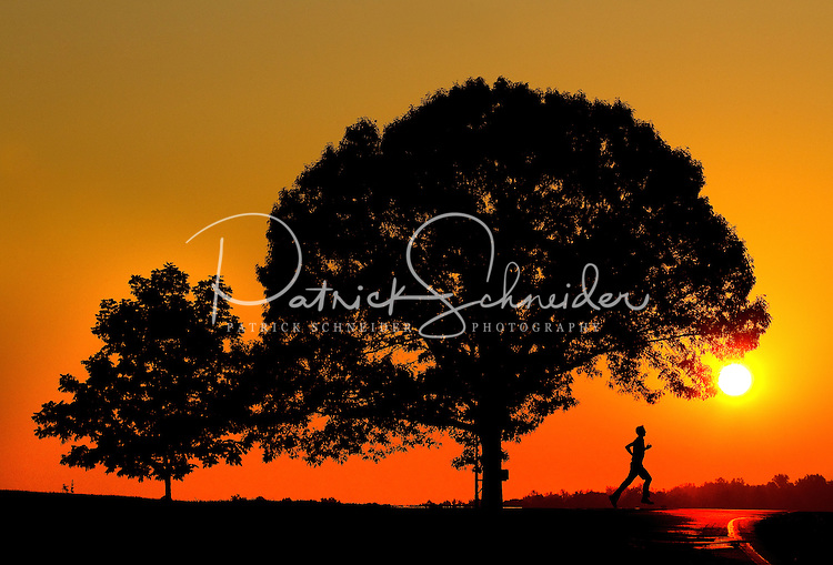 A runner is silhouetted against an early morning sunrise as he runs along a North Carolina road near Statesville, NC. Model released image.