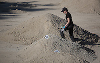 Pictured: A forensics officer next to some of the piles of soil that need to be searched through by in Kos, Greece. Thursday 06 October 2016<br />