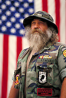 Vietman war veteran stands before the American flag, memorial, man, men, male, patriotism MR#999. Restrictions may be waived--contact photographer.