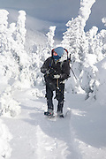 Appalachian Trail - A hiker photographing along the Carter-Moriah Trail in winter conditions near the summit of Carter Dome in the White Mountains, New Hampshire USA