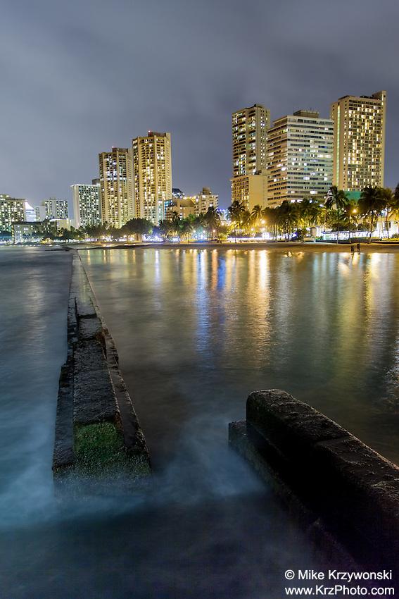 "Hotels with lights reflecting off the water at night at Kuhio Beach (aka ""Walls"") in Waikiki, Oahu"