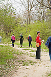 Mature female friends start to walk into William Faulkner's woods in Oxford, Mississippi as one woman in red turns to wait for friend