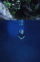 Diver swimming through cave