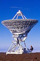 Man on cel phone with laptop near radio telescope on Mauna Kea, Big Island of Hawaii