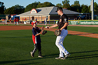 Batavia Muckdogs catcher Gunner Pollman hands the ball to a young fan after the ceremonial first pitch before a NY-Penn League game against the Auburn Doubledays on August 31, 2019 at Dwyer Stadium in Batavia, New York.  Auburn defeated Batavia 12-5.  (Mike Janes/Four Seam Images)