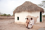 25 JULY 2011: Basti Mahraan Village, Punjab, Pakistan.    Mahar Abdul Latif (R), a former member of Muslim terrorist group Lashkar-i-Taiba (LeT) at his home village of Basti Mahraan in Pakistan with fellow villager Bachu Ram, a Hindu. After Ram offered to donate his rare blood type to save the life of a Muslim woman, relations thawed in the traditional violence between the Muslims and Hindu's of the village. The men are seated outside a Hindu temple that was renovated by the Muslim's of the village in a sign of solidarity.Picture by Graham Crouch/Toronto Star