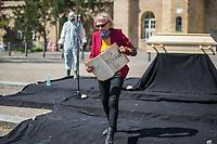 """Mit einer Protestaktion """"Trauerfeier fuer die Demokratie"""" protestierte am Sonntag den 26. April 2020 auf dem Berliner Mariannenplatz in Kreuzberg eine """"Aktion Eigensinn"""" gegen die Einschraenkungen im Zuge der Massnahmen zur Eindaemmung der Covid-19-Pandemie. Sie stellten einen Holzsarg auf forderten anwesende Menschen auf Plakate und Schilder abzulegen und Reden ueber die momentane Corona-Krisensituation zu halten. Bei diesen Reden wurden von Teilnehmern zum Teil Verschwoerungstheorien verbreitet, so sei z.B. die Krise ein lange vorbereiteter Plan der Regierenden und Freiheitsrechte einzuschraenken.<br /> Im Bild: Eine interessierte Frau hat ein selbstgemaltes Kondolenzbuch mitgebracht.<br /> 26.4.2020, Berlin<br /> Copyright: Christian-Ditsch.de<br /> [NUR FUER REDAKTIONELLE ZWECKE! Werbung nur auf Anfrage beim Fotografen. Inhaltsveraendernde Manipulation des Fotos nur nach ausdruecklicher Genehmigung des Fotografen. Vereinbarungen ueber Abtretung von Persoenlichkeitsrechten/Model Release der abgebildeten Person/Personen liegen nicht vor. NO MODEL RELEASE! Don't publish without copyright Christian-Ditsch.de, Veroeffentlichung nur mit Fotografennennung, sowie gegen Honorar, MwSt. und Beleg. Konto: I N G - D i B a, IBAN DE58500105175400192269, BIC INGDDEFFXXX, Kontakt: post@christian-ditsch.de<br /> Bei der Bearbeitung der Dateiinformationen darf die Urheberkennzeichnung in den EXIF- und  IPTC-Daten nicht entfernt werden, diese sind in digitalen Medien nach §95c UrhG rechtlich geschuetzt. Der Urhebervermerk wird gemaess §13 UrhG verlangt.]"""