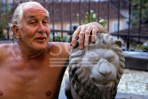 Rio de Janeiro, Brazil. Train robber Ronnie Biggs with a stone lion at his home in Santa Tereza in 1990.