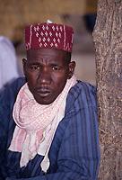 Zinder, Niger, West Africa.  Hausa Man in Blue Boubou, Maroon Hat.