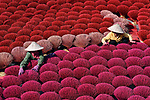 Workers arrange thousands of brightly coloured incense stick by Ly Hoang Long