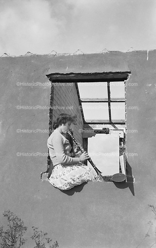 0405-J02 woman playing clarinet in window, Europe.