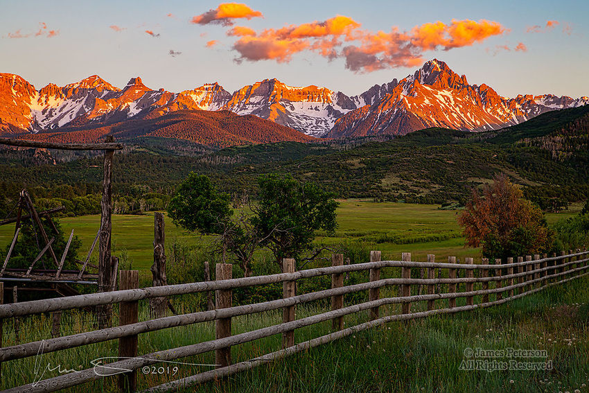 Sunset on The Sneffels Range.  Mount Sneffels and its compadres bask in the warm glow of the setting sun in this view along West Dallas road.  This spectacular ridge is in the northern part of the San Juan Mountains in southwestern Colorado, and offers stunning views from many directions.<br /> <br /> Image ©2019 James D Peterson