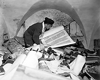 """In the cellar of the Race Institue in Frankfrut, Germany, Chaplain Samuel Blinder examines one of hundreds of """"Saphor Torahs"""" (Sacred Scrolls), among the books stolen from every occupied country in Europe.  July 6, 1945.  T3c. Irving Katz. (Army)<br /> NARA FILE #:  111-SC-209154<br /> WAR & CONFLICT BOOK #:  1100"""
