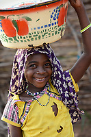CHAD, Goz Beida, refugee camp Djabal for refugees from Darfur, Sudan, Darfuri carry carry a enamel bowl on the head / TSCHAD, Goz Beida, Fluechtlingslager Djabal fuer Fluechtlinge aus Darfur, Sudan