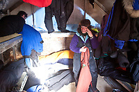 Rookie Michelle Phillips wipes some sleep from her eyes inside the 10'x12' musher sleeping quarters at the Cripple checkpoint 1/2 way into the race during the 2010 Iditarod