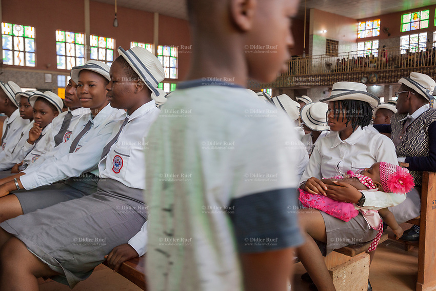 """Nigeria. Enugu State. Enugu. St. Theresa's Parish. Catholic Church. A group of female students from """" Notre Dame Academy """" seat on wooden benches and follow the morning Sunday mass. """" Notre Dame Academy """" has a motto written on their white shirts: God is good. On of the young woman is already a mother and she holds her daughter in her arms during the religious service. Enugu is the capital of Enugu State, located in southeastern Nigeria. 30.06.19 © 2019 Didier Ruef"""