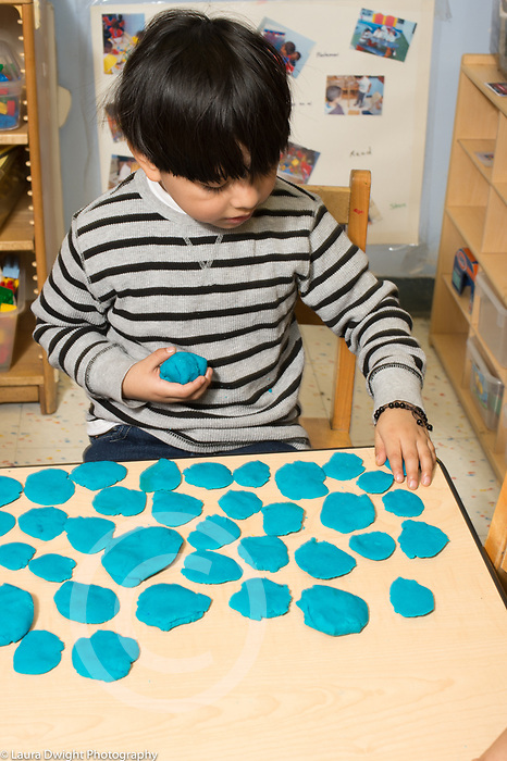 Education preschool 3 year olds boy making flattened circles of play dough on table