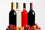 Four different wine bottles and grapes.  Red, white, rose, zinfandel.  White background.