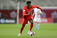 TORONTO, ON - OCTOBER 15: Alphonso Davies #20 of Canada dribbles with the ball during a game between Canada and USMNT at BMO Field on October 15, 2019 in Toronto, Canada.