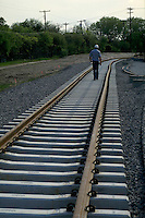 A supervisor inspects the work on a rail line under construction. Supervisor, Inspector.