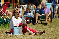 Pictured: A woman reads a book on the festival green during a warm sunny day.<br /> Re: Hay Festival at Hay on Wye, Powys, Wales, UK. Saturday 02 June 2018