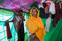 Bangladesh, Teknaf, Cox's Bazar. Leda Rohingya Refugee Camp. The Rohingya, a Muslim ethnic group  denied citizenship in Burma/Myanmar have escaped persecution from Burmese militants in their country. There are up to 500,000 refugees and migrants living in makeshift camps in Teknaf, Cox's Bazar. <br /> Setera (in the orange shawl) managed to escape from Myanmar two months ago (crying as she tells me the story). Three months ago they had seven children when the Myanmar military broke down the door to her house. She was standing with a baby on her hip, they burned down her house and threw her baby into the burning fire. She and her young daughter were raped repeatedly. Her husband was bady cut and her daughter's husband was taken to jail. They managed to escape. Her daughter, Jannatra is pregnant and came only three days ago. There is nothing for them to do here, they can't work. Her husband in the street as many are, just begging. The only thing they get from the Bengali government is some rice each month.