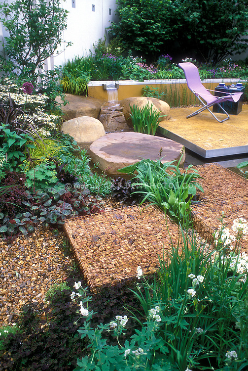 Deck backyard landscaping with unusual hardscaping materials: stones encased in wire mesh, boulders, furniture, waterfall water feature from raised bed, flowers Astrantia, shrubs, walkway path, garden scene view, lifestyle outdoors
