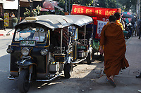 Monks passing by tuk tuk taxis and street food stand in Chiang Mai city , December 2016, after the kings death