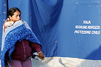 Una donna si ripara con una coperta nella tendopoli allestita per accogliere gli sfollati, in piazza d'Armi, all'Aquila, in Abruzzo, 8  aprile 2009, dopo il terremoto che ha colpito la regione..A woman protects herself from the cold with a cover, in a tent-camp set up by the civil protection agency, in L'Aquila, central Italy, 8 april 2009, to put up survivors of the earthquake that hit the region Abruzzo..UPDATE IMAGES PRESS/Riccardo De Luca