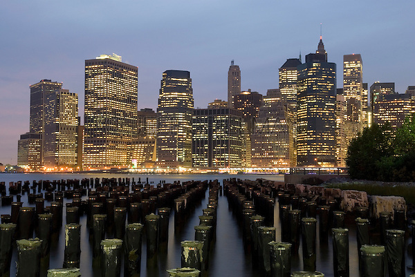 AVAILABLE FROM WWW.CORBIS.COM FOR LICENSING.  Please go to www.corbis.com and search for image # 42-31907789.<br /> <br /> Lower Manhattan Financial District Skyline and Wooden Posts in the East River at Dusk, Viewed from Brooklyn, New York City, New York State, USa