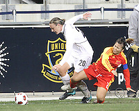 Abby Wambach #20 of the USA WNT is tackled by Huana Liu #2 of the PRC WNT during an international friendly match at PPL Park, on October 6 2010 in Chester, PA. The game ended in a 1-1 tie.