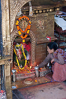 Kathmandu, Nepal.  Lady Giving Offering at a Neighborhood Temple to Ganesh.