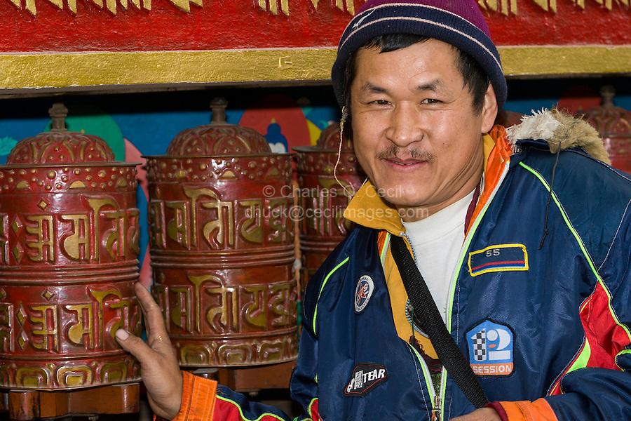 Nepal, Kathmandu, Swayambhunath.  Buddhist Man about to Spin a Prayer Wheel.