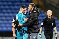 Bolton Wanderers' goalkeeper/coach Matthew Gilks (left) is congratulated on victory and keeping a clean sheet by Salford City's goalkeeping coach Carlo Nash <br />
