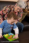 2 year old toddler boy at home with grandmother playing with puzzle encouraged to play with it language development talked to vertical Caucasian she takes care of him when parents work