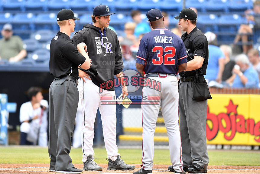 Asheville Tourists pitcher Riley Pint (32) and Rome Braves coach Anthony Nunez (32) exchange lineups and discuss ground rules with umpires Reed Basner and John Benken before a game at McCormick Field on June 12, 2017 in Asheville, North Carolina. The Tourists defeated the Braves 7-0. (Tony Farlow/Four Seam Images)