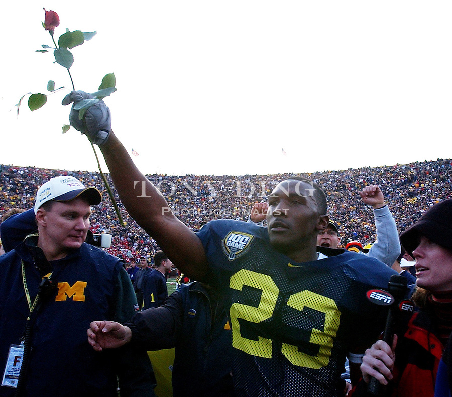 Michigan senior running back Chris Perry (23) holds up a rose after the Wolverine's 35-21 upset of Ohio State on Saturday, November 22, 2003 in Ann Arbor, Mich. This was the 100th rivary match between UM and OSU. (TONY DING/The Michigan Daily)