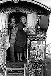 Appleby in Westmorland Horse fair Cumbria. 1981. These women tell fortunes. the photographs show their clients supposedly. Image in centre is of Prince Charles. 1981. A traditional Bow top wagon.