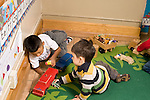 Education preschoool children ages 3-5 two boys playing with wooden truck, human figures on rug playing together horizontal