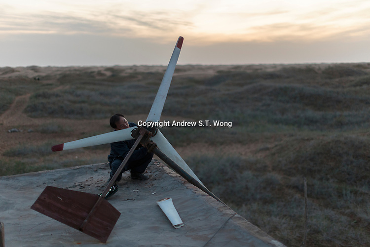 A local farmer, who are practising eco-agriculture, tries to fix a wind turbine on the rooftop of his house in Alxa Left Banner, Inner Mongolia, China, October 2017.