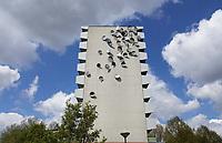 Nederland Amsterdam - 2020. De Bijlmer. Kunst in de Bijlmer. Een 38-tal roestvrijstalen schotels op de kopgevel van flat Groeneveen. Een aantal van de schalen is voorzien van foto's van stadsilhouetten; daken, torens en telefoonkabels. De ongeordende beelden contrasteren met de weidsheid van de wolkenlucht en met de utopische ordening van de oude Bijlmerarchitectuur. Het kunstwerk is gemaakt door Rein Jelle Terpstra.   Foto : ANP/ Hollandse Hoogte / Berlinda van Dam