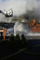 1992 File Photo Montreal (Quebec) CANADA<br /> Firemen create a rainbow while directing the water jet toward a burning old factory buiding,  No model release<br /> Photo (c) P Roussel / Images Distribution