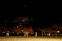 People play football in the sand on Urca beach at night