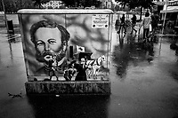Switzerland. Geneva. Rainy day on Plaine de Plainpalais. People walking with umbrellas. Painting about the International Red Cross (ICRC) and its founder Henry Dunant on an electrical switchboard. Henry Dunant (born Jean-Henri Dunant; 8 May 1828 – 30 October 1910), also known as Henri Dunant, was a Swiss humanitarian, businessman and social activist. He was the visionary, promoter and co-founder of the Red Cross. During a business trip in 1859, Dunant was witness to the aftermath of the Battle of Solferino in modern-day Italy. He recorded his memories and experiences in the book A Memory of Solferino which inspired the creation of the International Committee of the Red Cross (ICRC) in 1863. The 1864 Geneva Convention was based on Dunant's idea for an independent organisation to care for wounded soldiers. In 1901 he received the first Nobel Peace Prize, making Dunant the first Swiss Nobel laureate. The International Committee of the Red Cross (ICRC) is a humanitarian institution based in Geneva, Switzerland, and a three-time Nobel Prize Laureate. State parties (signatories) to the Geneva Convention of 1949 and its Additional Protocols of 1977 (Protocol I, Protocol II) and 2005 have given the ICRC a mandate to protect victims of international and internal armed conflicts. Such victims include war wounded, prisoners, refugees, civilians, and other non-combatants.13.06.2020  © 2020 Didier Ruef